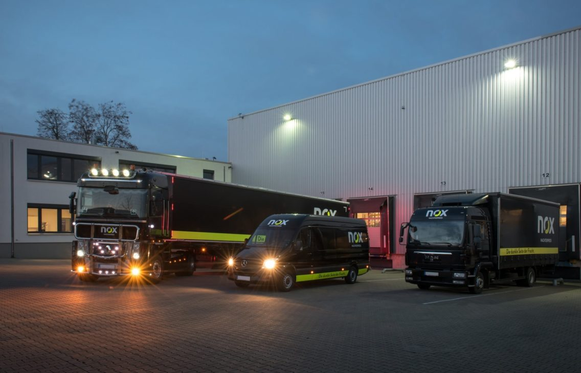 Trucks and cars at a parking space by night